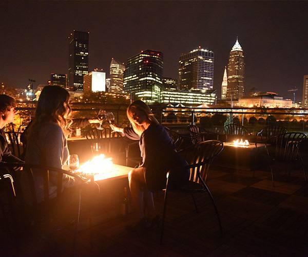 LeanDog Boat wine on the patio with a fire cleveland in background