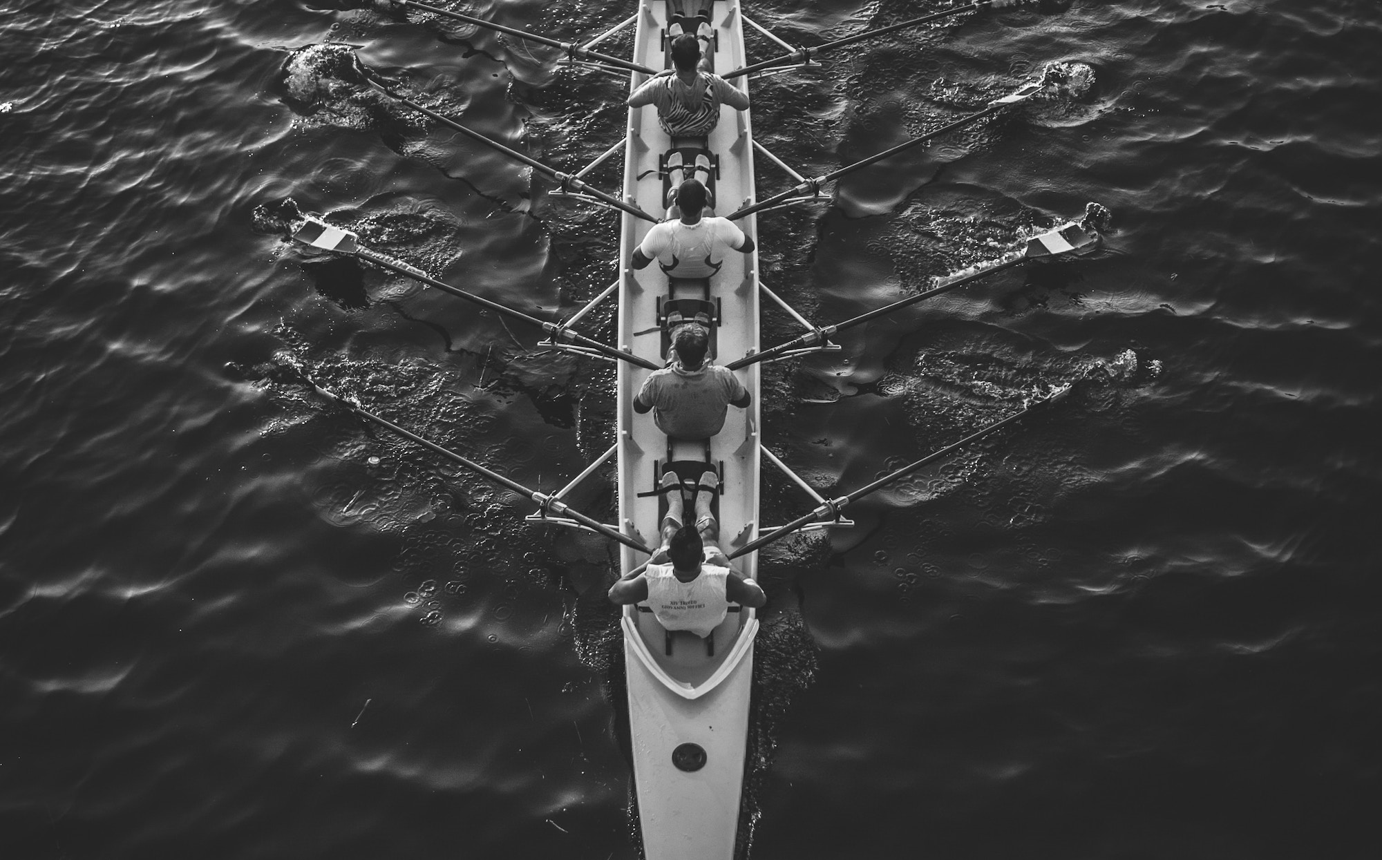 crew rowing together grayscale
